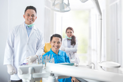 portrait of dentists and his assistant smiling with male patient in dental clinic